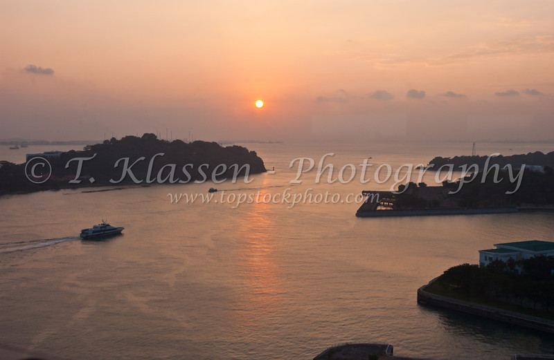 Sunset over the harbour at Singapore, East Asia.