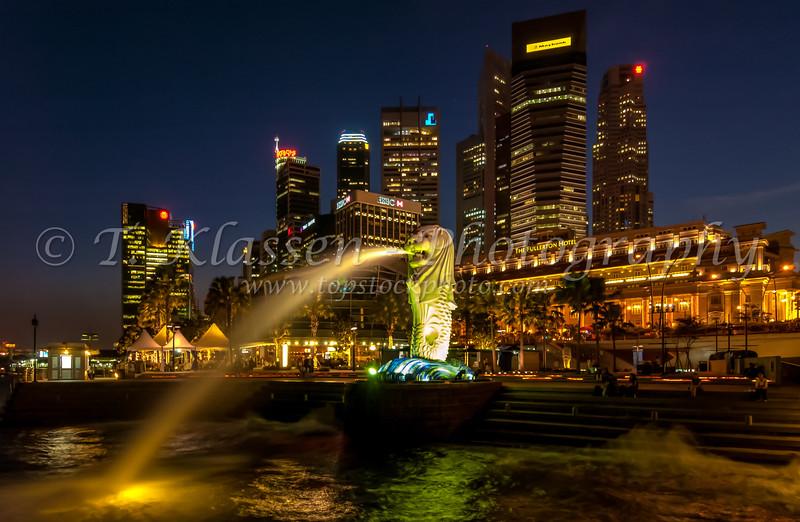 The city skyline of Singapore at dusk with illuminted Merlion, Asia.