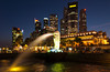 The Merlion fountain and downtown skyline at dusk in Singapore, East Asia.