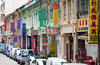 A street scene with traffic and shop fronts in Little India in Singapore, East Asia.