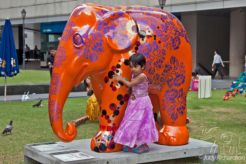 Young girl enjoying the elephant along the river walk in Singapore.
