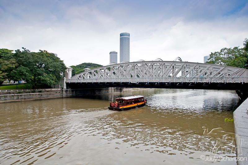 Tourist boat going under bridge.