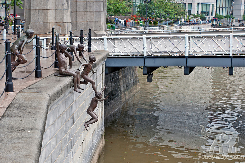 """Charming statues pop up all along the Singapore River Walk. These """"boys"""" are enjoying a hop into the river."""
