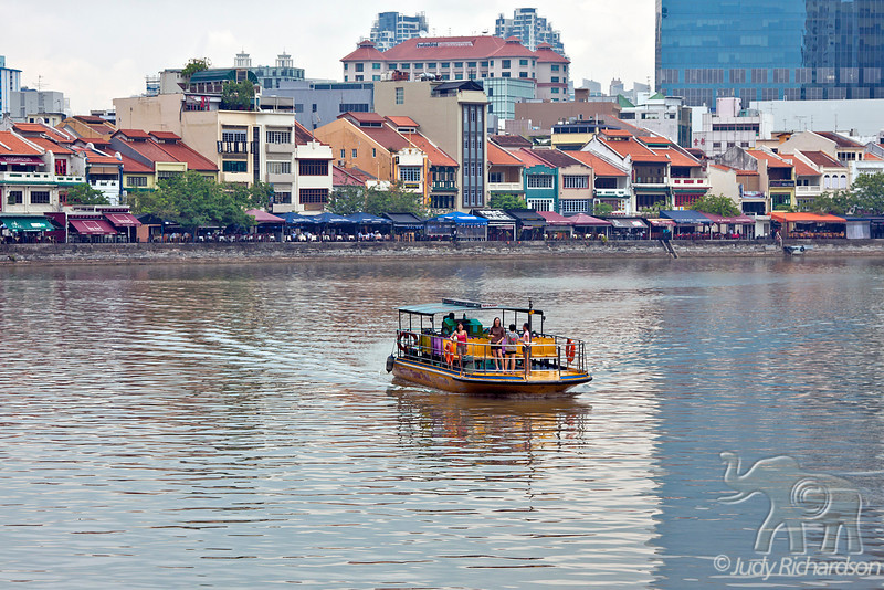 Tourist boat along the Singapore River. In the background along the river are numerous outdoor eating stalls.