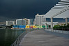 Dark thunderous skies set off the Marina Bay walk, colorful event stands, and upscale hotels.