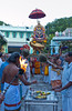 Thaipusam ritual procession in Singapore depicting carrying of Kevadis down the street, body piercing, devotees attending the Kevadi carrier, Procession of the Lord Muruga on Golden Peacock Vaganam in the Thendayuthapani Temple.