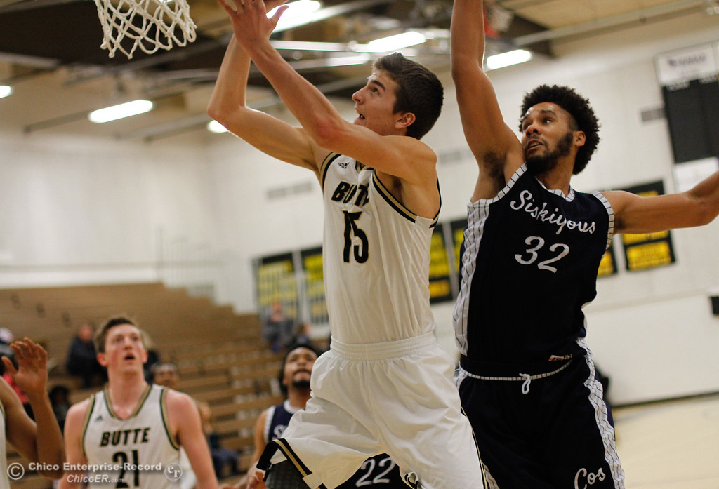 . Butte College\'s Jared Stidham (left) goes up for a shot as Siskiyous\'s Deontrey Fuller tries to block his shot during a men\'s basketball game January 23, 2017 at Butte College in Oroville, California. (Emily Bertolino -- Enterprise-Record)