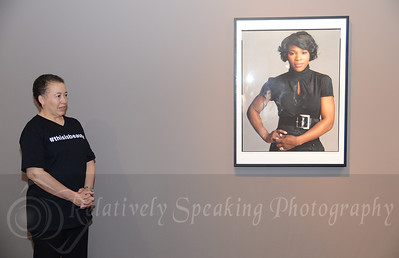 Dr. Tatum is standing next to a beautiful photo of tennis player Serena Williams.