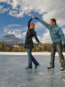 Couple ice skating on frozen Mildred Lake at The Fairmont Jasper Park Lodge near Jasper, Alberta, Canada.