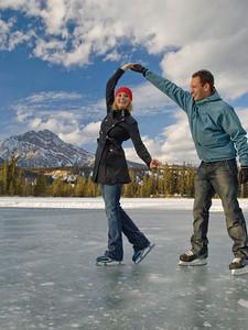 Couple ice skating on frozen Mildred Lake at The Fairmont Jasper Park Lodge near Jasper, Alberta, Canada.