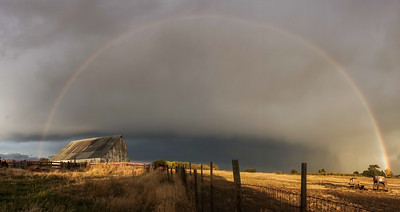 Old Barn under rainbow and storm clouds