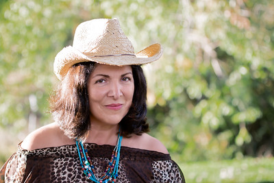 Portrait of a woman with dark hair in a straw hat.