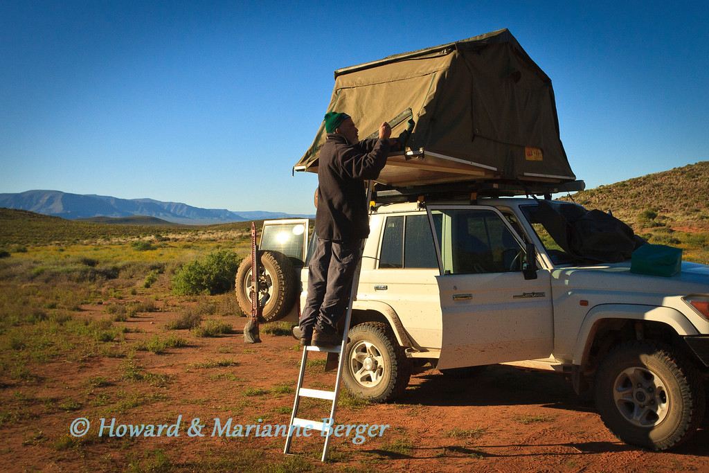 """<h2>Sleeping up top?</h2> <b>Roof top tent versus ground tent.</b> We prefer the roof top tent (RTT).  At first we did set up a small bell tent, if staying for a number of days in a fenced camp, to allow us more space in the LC76SW  and allow quicker sunrise departures. However after 7 years of 6 months a year practice I get the tent up or down in 5 minutes. In good weather that is! When its freezing, tucking in frozen flaps  is painful; and in the rain and dark careful slow steps are advised. But we find it very comfortable, with good mosquito protection, and feel much safer high up in the non-fenced camping areas. The toilet facilities have been discussed above.. Do remember to varnish the wood, re-waterproof the canvas, and have a few spare bolts for the aluminium poles/hinge fittings (the latter was a one off problem years ago). We have had 7 years of fantastic service from this tent, with amazing help from the manufacturers for small adjustments e.g. adding velcro to sideflaps to allow easier opening of ventilation flaps. As we drive off first thing in the morning and I dont feel like removing metal supports from flaps in the dark.  <b>LIGHTNING DANGER:</b>  No  tent is safe. Get back into your car and be protected by the """"Faraday cage"""" phenomenon. See our detailed discussion at www.lightningsafety.com and www.landcruiserclub.co.za (search under """"RTT and lightening"""". Simple rule that is advocated is:""""30-30"""" rule: take shelter if the time from seeing a flash to the time you hear thunder is 30 seconds or less, and don't resume activities until 30 minutes have elapsed from the last lightning and thunder.  The scene is beautiful Schaapwagterspos Camping site, Tankwa National Park,  South Africa, we had just discovered that the zip of the mosquito net door was broken after 7 years hard wear(it is hidden by canvas door cover). This was right at the beginning of our 6 month trip in 2011. Luckily this was not in the major mosquito season (Notice the winter clothes)"""