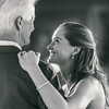 A bride looks up and smiles to her father during the daughter father dance at Belhurst Castle in Geneva, NY.