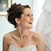 A bride laughs as her bridesmaid peaks under her dress.