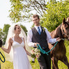 The bride and groom walk with their horses on their family farm in Hamilton, NY.