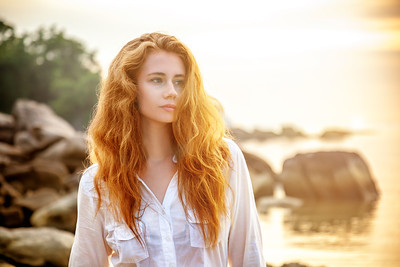 Beautiful young woman with long red hair on the beach at sunset background