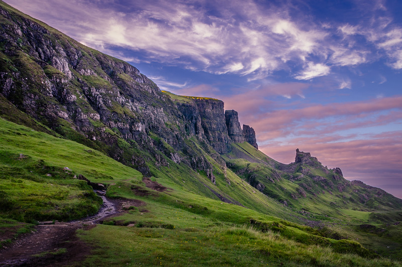View on Quiraing hiking trail along the high cliffs during sunset with pink clouds on blue sky, Isle of Skye, Scotland
