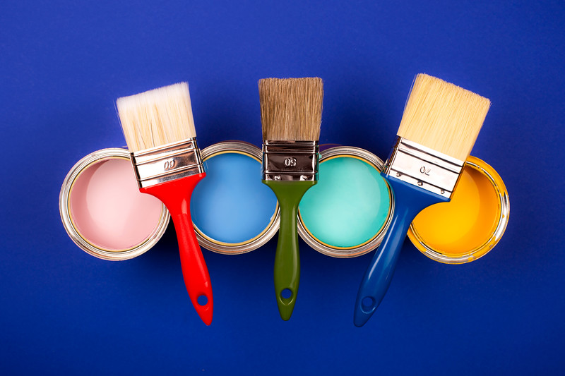 Four open cans of paint with brushes on bright background.