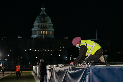 A worker puts finishing touches on a giant American flag on the National Mall ahead of inauguration