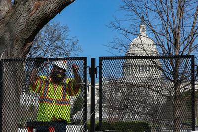 Worker removes barbed wire from fence around Capitol