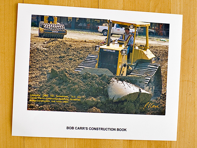 """Printing the caption on the photo is another good way to print construction photos. The caption is always with the photo, good or bad. <br /> <br /> I pasted the .jpg file into MS Word. I then added a text box, in which I pasted the caption I had copied from MyConstructionPhotos. I highlighted the text box, right clicked to get Format Text Box Window, clicked """"In front of text"""" to place text box in front of the photo. I selected a text box font color I liked, a yellow to match Caterpillar's. Here is the result. All this is illustrated in a following figure."""