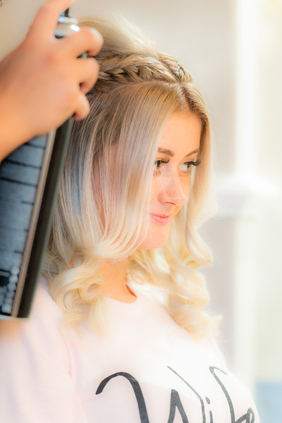 Bride looking happy as her hair is finished