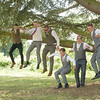 The groomsmen jump from a tree smiling and laughing