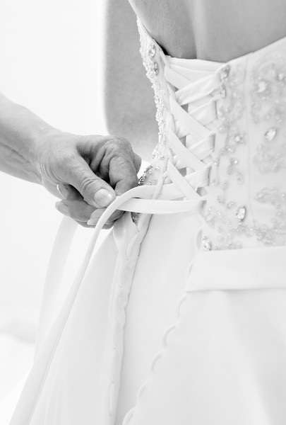 The brides mother ties her daughters dress