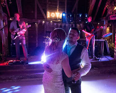 The bride and groom dance in front of the live wedding band