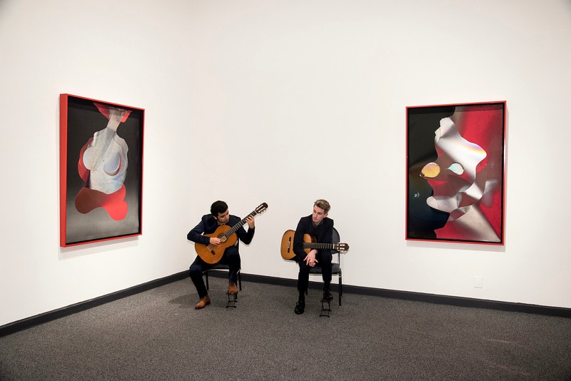 Guitarists at a gallery.