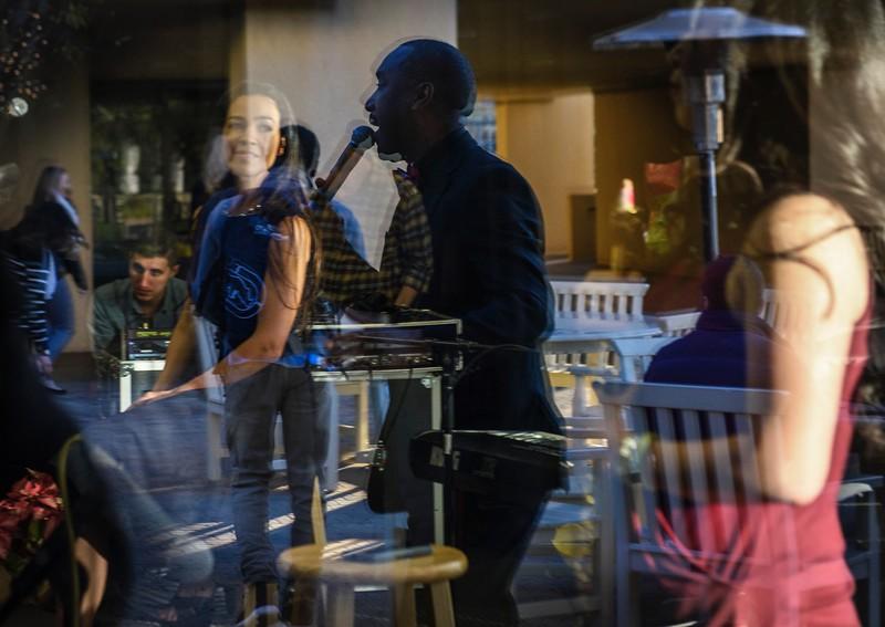 Man singing at outdoor restaurant.