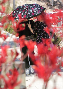 Two women walking with an umbrella in Malibu California.