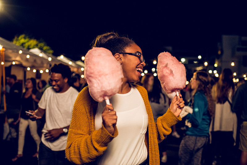 A girl brings cotton candy to a friend at a  carnival in Malibu, CA.
