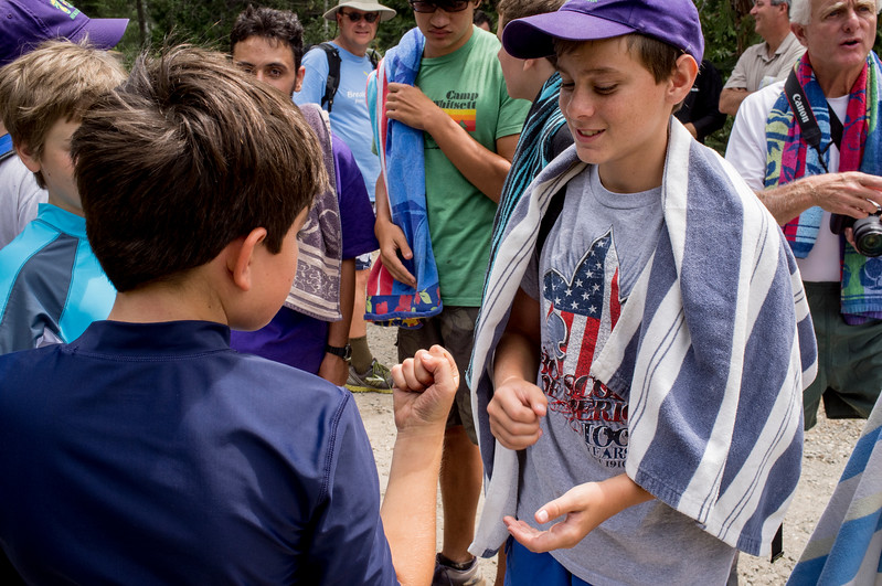 Two boy scouts  playing rock paper scissors.