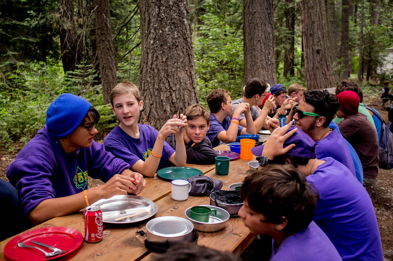 Boy Scouts having dinner at camp.