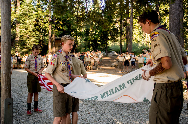 Boy Scouts folding the camp flag at a closing ceremony.