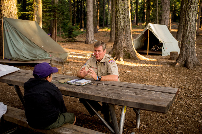 Boy Scout taking a merit badge test with a camp counselor.
