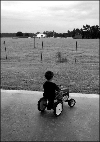 Young boy on a play tractor, Andrews South Carolina.