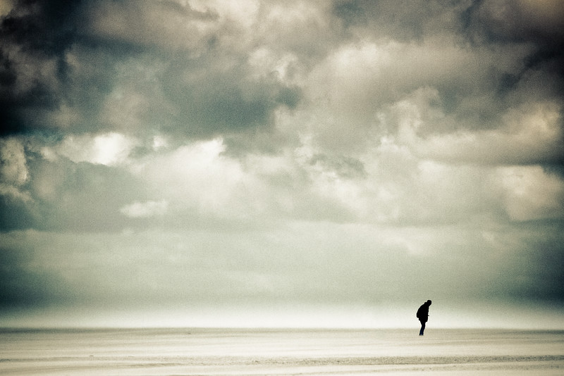 Man is walking on the beach through a storm with dark clouds