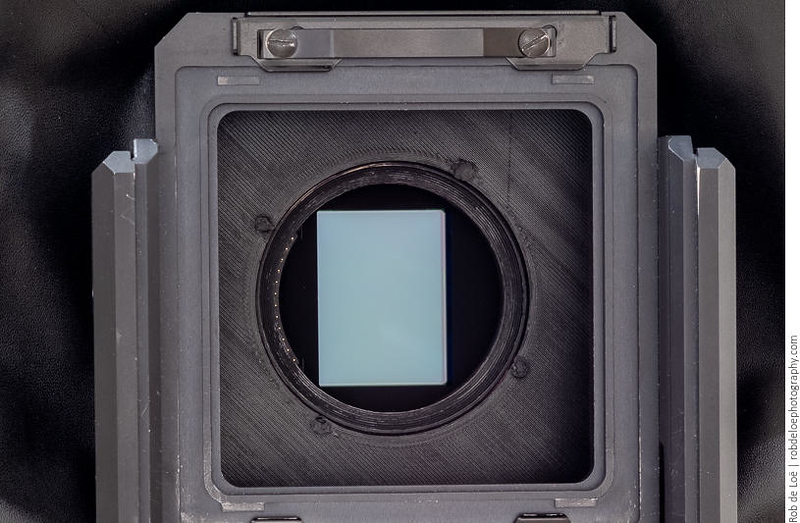 The Fuji GFX 50R sensor, seen from the front. The piece from the Fotodiox adapter is held to the camera board with four screws that are recessed into the board. The holes are filled and painted. Importantly, the weight of the camera is carried on the milled rim of the adapter, which rests on the inside of the hole. The screws simply hold the two pieces together.