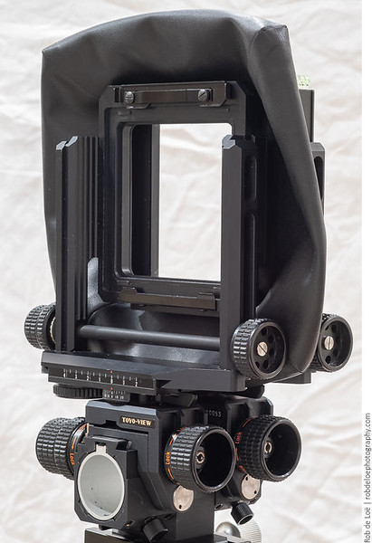 The bellows is a leather, bag-style unit. It attaches to the standards using clips that look similar to the ones visible here, which are for lens boards.