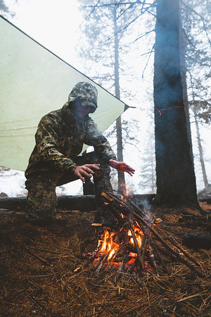 Austin Heinrich (no social) warming up after a cold rain in Idaho while mule deer backpack hunting.