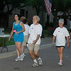 Bishop Rev Mark  Hanson center and his wife,Ione (right) cross the finish line during the 4k Run Walk & Roll Thursday morning. Photo by Mike Levin.