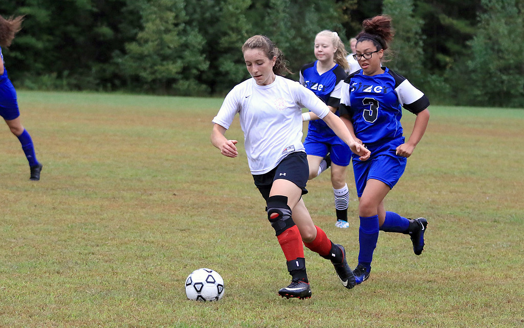 . Sizer School girls soccer played Trivium on Wednesday afternoon at Saima Park in Fitchburg. Trivium\'s Emma Scheurer takes off with the ball followed by Sizer\'s Naomi Matta-Paskal during action in the game. SENTINEL & ENTERPRISE/JOHN LOVE