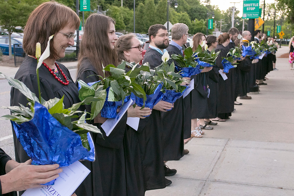 . The Sizer A North Central Charter Essential School held their graduation on Thursday night, June 6, 2019 at Fitchburg State University. Faculty and staff wait for the graduates outside to give each one a flower at the end of the ceremony. SENTINEL & ENTERPRISE/JOHN LOVE
