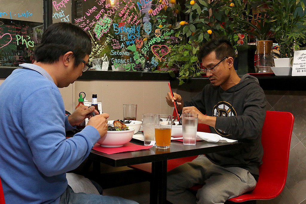 . Diners Matt Delorie of Ayer, on left, and Sopol Phan of Lowell enjoy their meal of mussels at the Sizzling Kitchen in Lowell on Merrimack Street. Delorie was having linguini and mussels and Phan was having the dish Mussells Fra Diavolo. SUN/JOHN LOVE