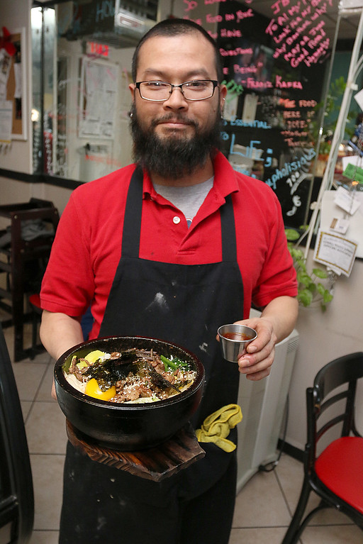 . Owner Lowell Nguyen hold the dish Bibimbap at the Sizzling Kitchen in Lowell on Merrimack Street. SUN/JOHN LOVE