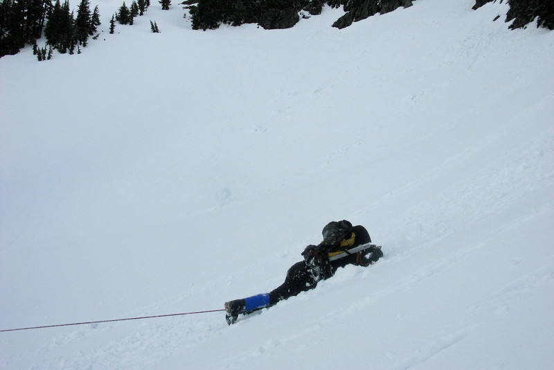 Prone with ice axe dug in to stop.  Notice the picket attached to the pack that will then be removed and driven int he snow to provide a safe place to clip the rope into.