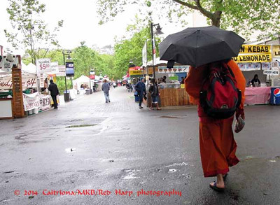 Monk with backpack and unbrella walks through Folklife